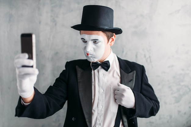 L'attore della pantomima con la maschera per il trucco fa selfie