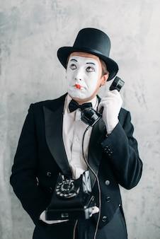 Attore di teatro pantomima con maschera per il trucco che si esibisce con il telefono retrò.