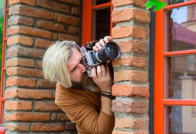 Paparazzi che fotografano l'uomo con la macchina fotografica scattano una foto spia spia spia dei mass media sotto copertura spia