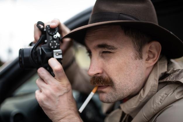 Paparazzo fotografo, detective che usa la macchina fotografica in macchina