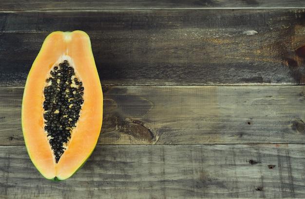 La papaia tagliata a metà su fondo di legno. copia spazio. vista dall'alto.