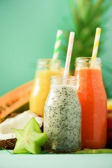 Papaia, frutta del drago, ananas, frullato di mango in barattoli. disintossicazione, alimenti dietetici vegani, concetto di mangiar sano. succo fresco in bottiglie di vetro su foglie di palma.