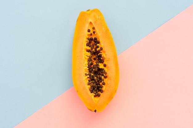 Frutta della papaia isolata sul rosa e sul blu