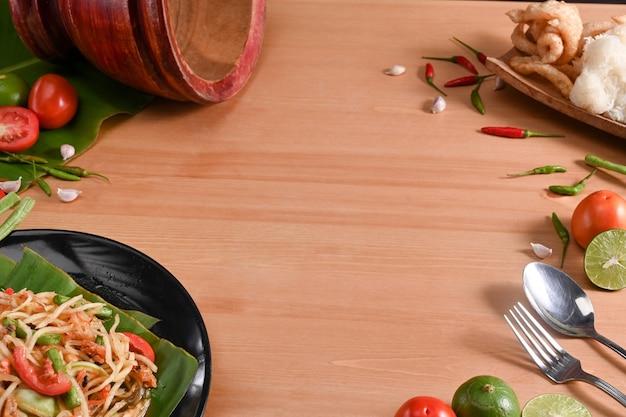 Insalata di papaia, ingredienti e mortaio su fondo di legno. concetto di cibo tailandese.