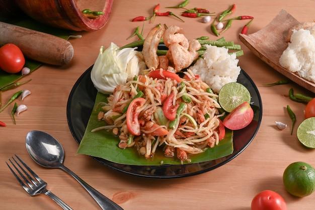 Insalata di papaya con riso appiccicoso sulla banda nera. concetto di cibo tailandese