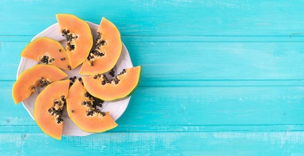 Fette di papaia sulla piastra su fondo di legno blu. copia spazio. vista dall'alto.