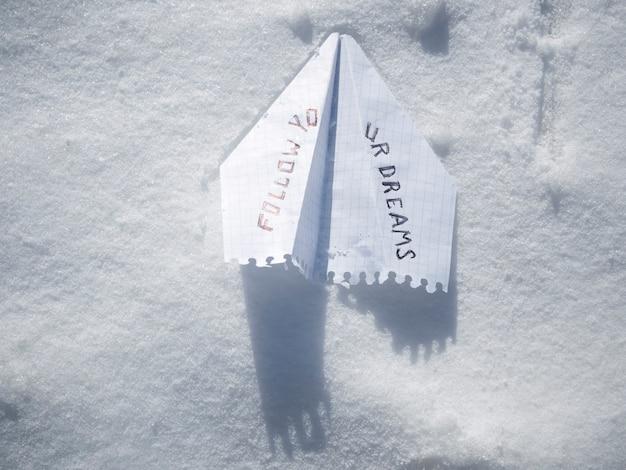 Aeroplano di carta sulla neve bianca con frase segui i tuoi sogni