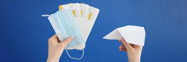 Aeroplano di carta con biglietti e maschera medica protettiva nelle mani su sfondo blu