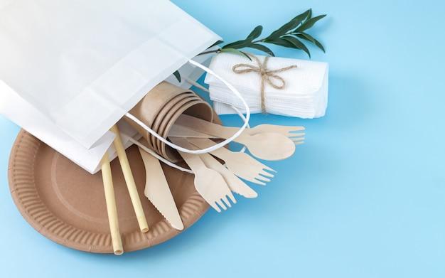 Sacco di carta pieno di stoviglie usa e getta eco friendly sulla scrivania blu