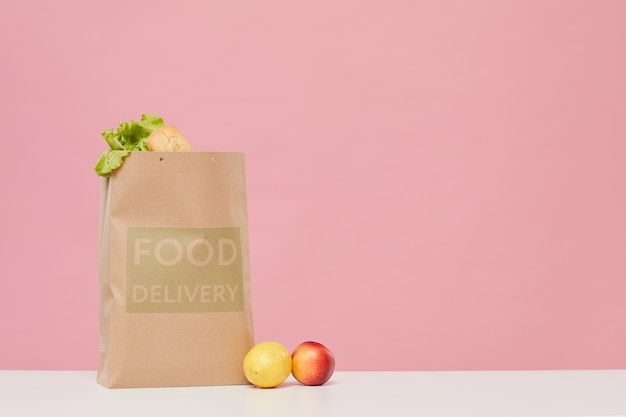 Sacchetto di carta pieno di frutta e verdura sul tavolo contro lo sfondo rosa
