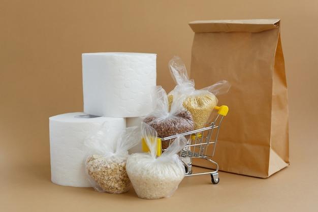 Sacco di carta carta igienica e vari semole in sacchetti in un carrello della spesa su uno sfondo marrone