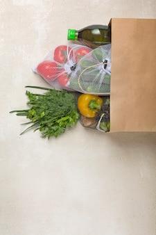 Consegna di verdure in sacchetto di carta dal supermercato. verdure fresche ed erbe aromatiche, consegna degli ordini tramite internet