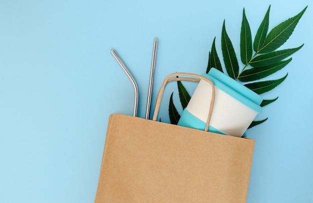 Sacchetto di carta con tazza di bambù e cannucce riutilizzabili su sfondo blu.