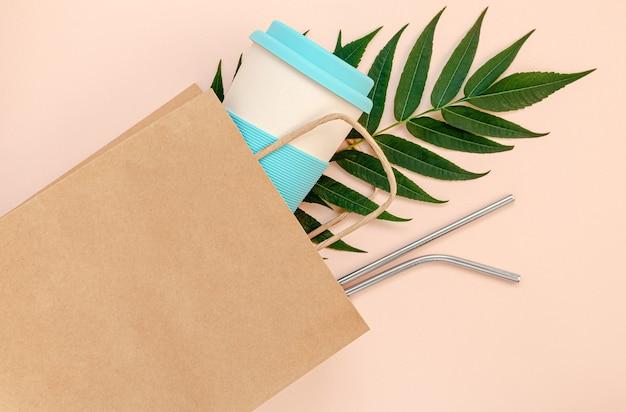 Sacchetto di carta con tazza di bambù e cannucce riutilizzabili su sfondo rosa