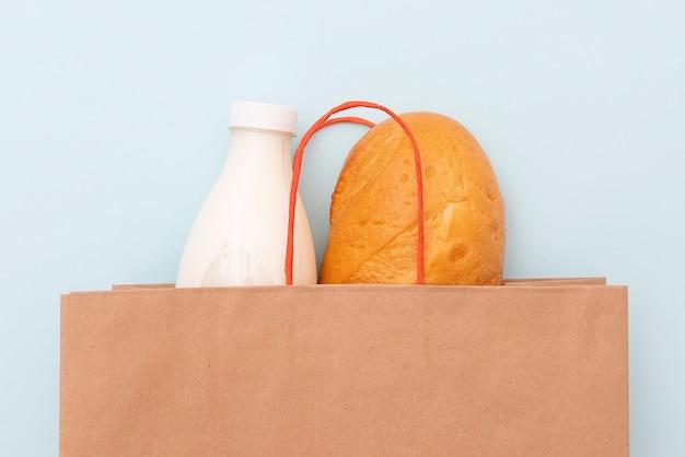 Sacco di carta con bottiglia di latte e pagnotta, pane bianco su sfondo blu