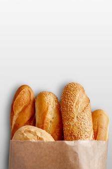 Un sacco di carta con pane sullo sfondo grigio.