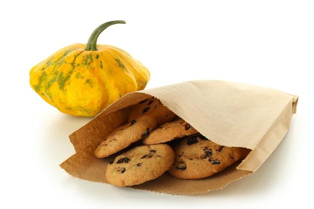 Sacco di carta con biscotti e zucca isolati su sfondo bianco.