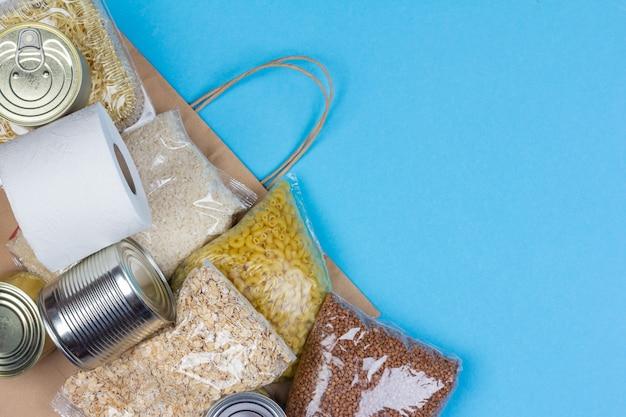 Sacco di carta con una fornitura alimentare di crisi per il periodo di isolamento in quarantena coronavirus, riso, pasta, farina d'avena, cibo in scatola, carta igienica, grano saraceno su sfondo blu