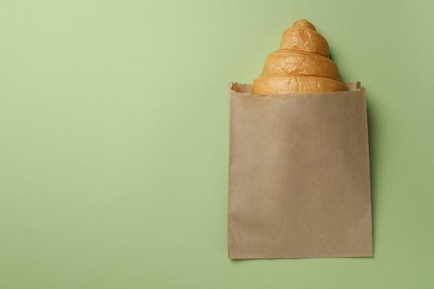 Sacco di carta con croissant sul verde