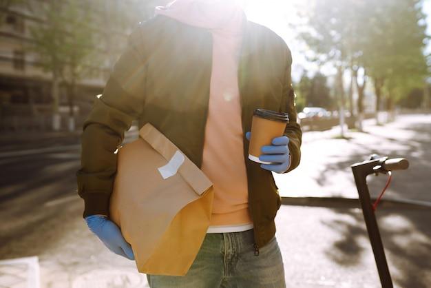 Il sacchetto di carta con cibo e caffè nelle mani del corriere nella città di quarantena. servizio di consegna in quarantena, epidemia di malattia, condizioni pandemiche di coronavirus covid-19.
