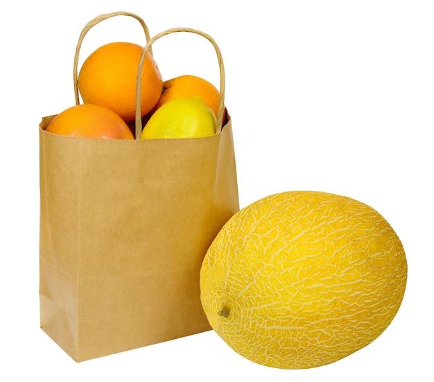 Sacco di carta con frutta e melone giallo isolato su bianco. dieta vegetariana e alimentazione sana