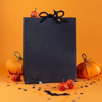 Sacchetto di carta con decorazioni di halloween, zucche, pipistrelli, coriandoli, shopping natalizio e concetto di vendita