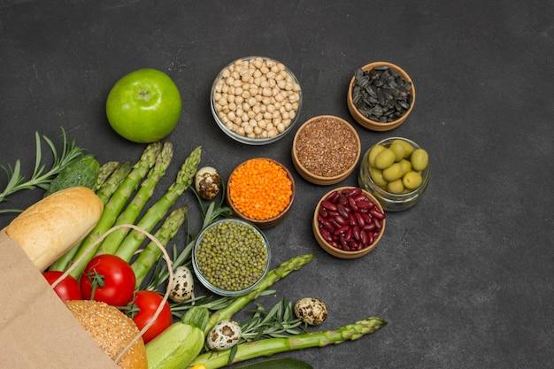 Sacchetto di carta con verdure, fagioli noci, quinoa bulgur, ceci, lino mandorle. sfondo nero