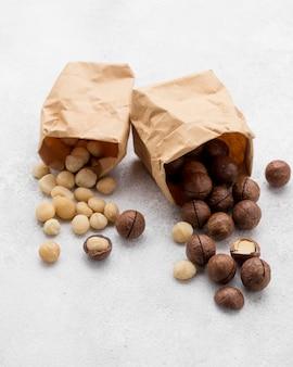 Sacchetti di carta pieni di noci di macadamia e rotoli di cioccolato