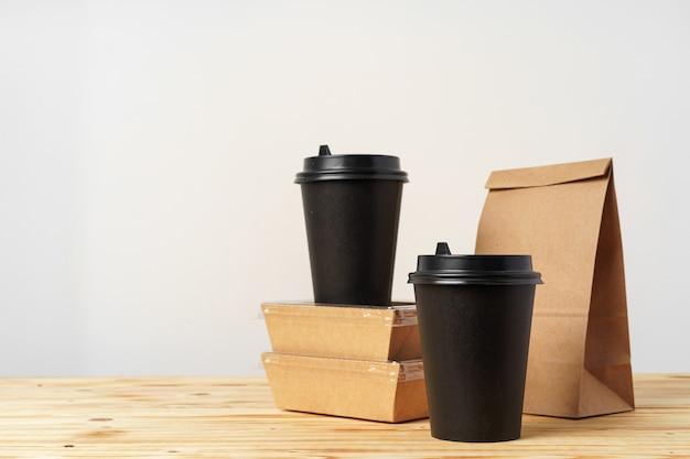 Sacchetti di carta con contenitori per cibo da asporto e tazzine da caffè. sacco per il pranzo