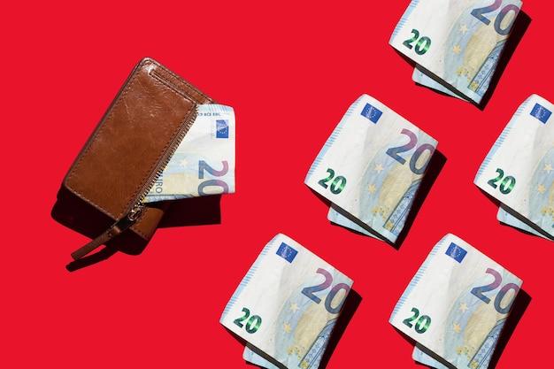 Fatture cartacee di 20 euro e un portafoglio su uno sfondo rosso concetto di contanti