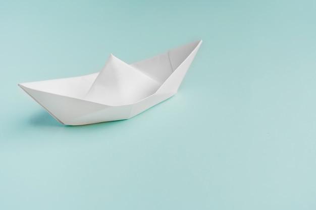 Barca di carta su uno sfondo azzurro, spazio per il testo
