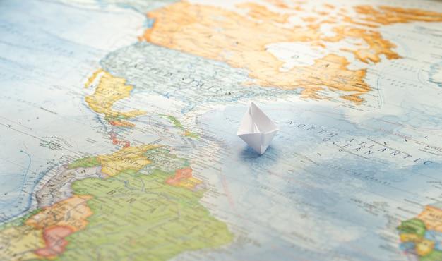 Barca di carta che naviga sull'oceano