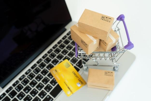 Scatola di carta su un computer portatile, concetto in linea di acquisto facile