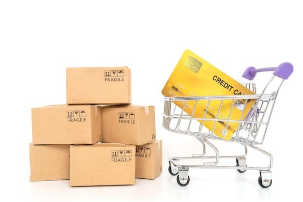 Scatole di carta e un carrello su sfondo bianco. shopping online o concetto di ecommmerce e concetto di servizio di consegna con lo spazio della copia