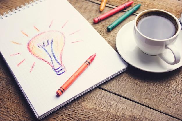 Carta, lampadina, smartphone, penna e tazza di caffè sulla scrivania in legno