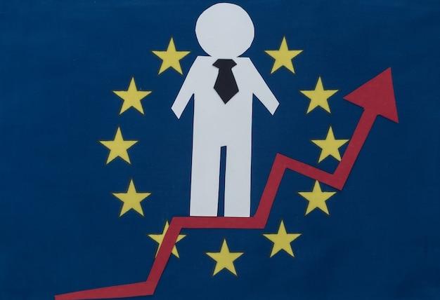 Uomo d'affari di carta con freccia di crescita sulla bandiera dell'ue. simbolo di successo finanziario e sociale, scala di progresso. scala di carriera.