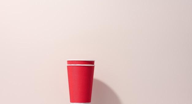 Tazze rosse di cartone di carta per caffè, fondo beige. stoviglie ecologiche, zero sprechi