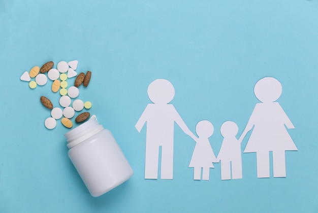 Famiglia della catena di carta, pillole della bottiglia sul blu, concetto di assicurazione sanitaria
