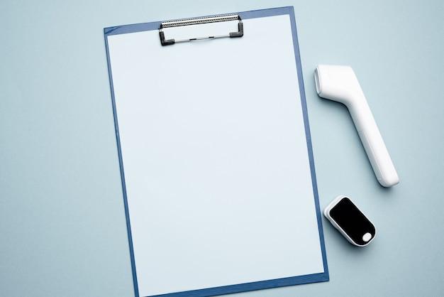 Appunti di carta e termometro elettronico senza contatto in plastica bianca e misuratore di ossigeno nel sangue, sfondo blu