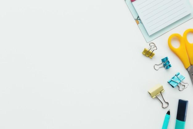 Graffette, orologio meccanico, pennarello e matita, forbici su sfondo bianco. concetto di lavoro e istruzione.
