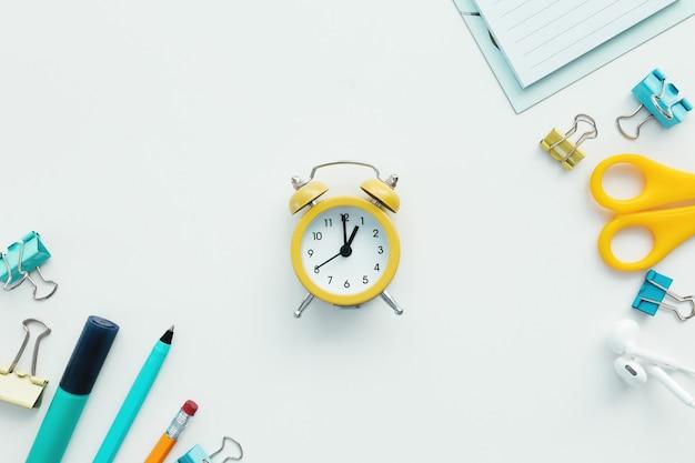 Graffette, orologio meccanico, penna, matita e blocco note, forbici e auricolari su sfondo bianco. concetto di lavoro e istruzione