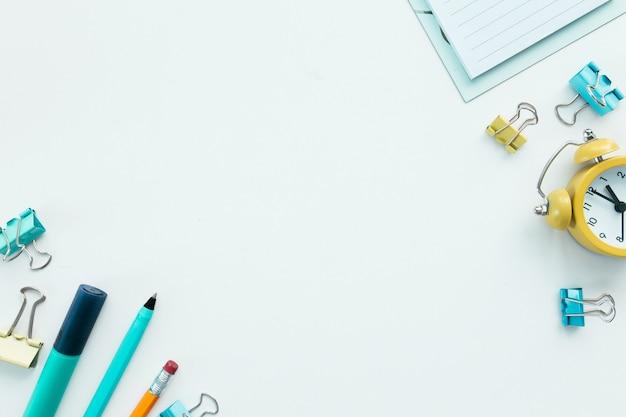 Graffette, orologio meccanico, penna, matita e blocco note su sfondo bianco. concetto di lavoro e istruzione