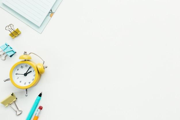 Graffette, orologio meccanico, penna, matita e blocco note su sfondo bianco. concetto di lavoro e istruzione.