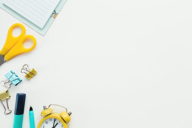Graffette, orologio meccanico, matita, forbici su sfondo bianco. concetto di lavoro e istruzione.