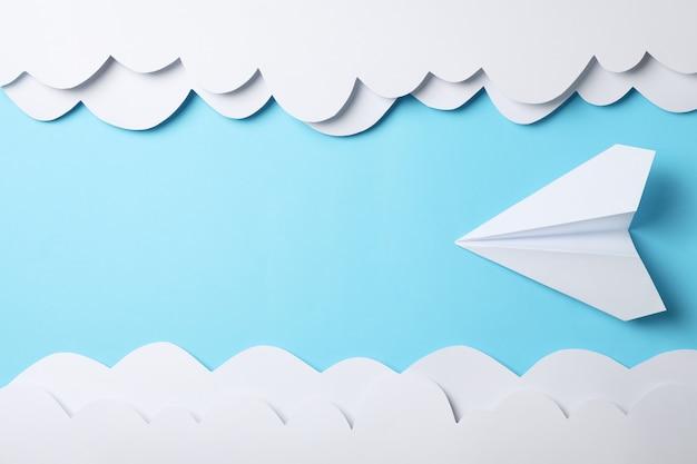 Nuvole ed aereo di carta sul blu. viaggio
