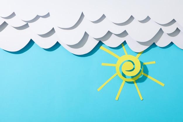 Nuvole e sole di carta sul blu. viaggio