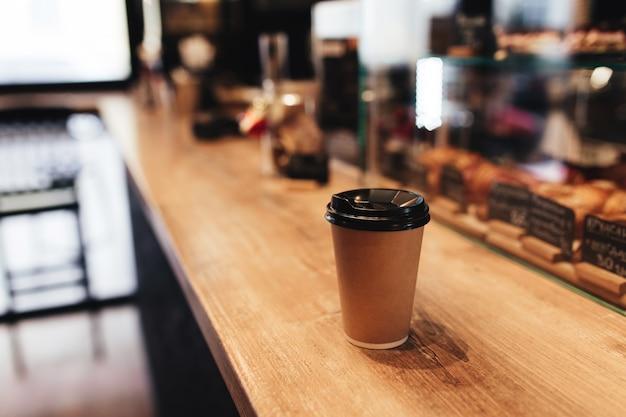 Tazza di caffè di carta sul bancone del bar nella caffetteria