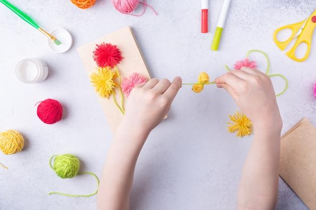 Mestieri di carta per la festa della mamma marzo o compleanno bambino piccolo che fa un mazzo di fiori di carta colorata e palline colorate per maglieria per la mamma semplice idea regalo vista dall'alto spazio copia foto di alta qualità