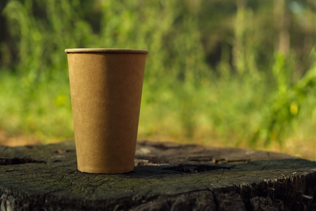 Bicchiere di carta di carta kraft marrone su un vecchio ceppo nel bosco.