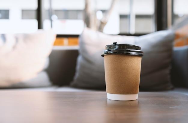 Bicchiere di carta di caffè sul tavolo nella caffetteria